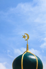 Gold islamic religious symbol on top of a mosque dome