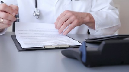 Doctor writing patient notes on a medical examination form