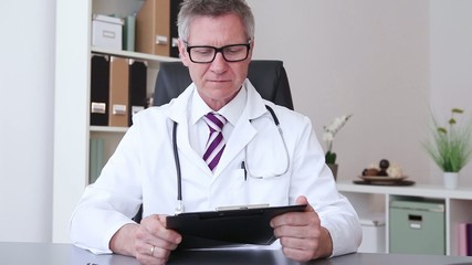 A male doctor sitting and giving a thumb down