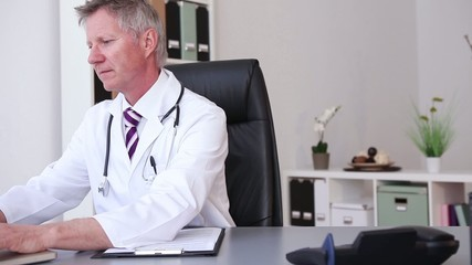 Doctor with stethoscope around his neck working at laptop