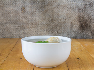 chicken soup in a cup with a sack on the table