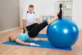 Instructor Looking At Woman Exerting poster