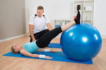 Instructor Looking At Woman Exerting