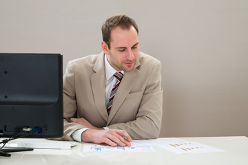 Businessman Analyzing Graph In Office