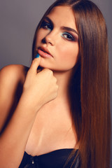 young woman with straight dark hair and bright makeup