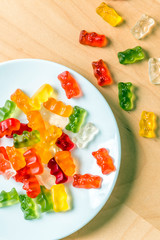 gummy bears on a white plate and wooden table