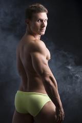 Handsome shirtless muscular man's back, turning around