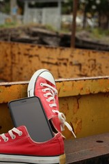 Red shoes with smart phone on yellow background