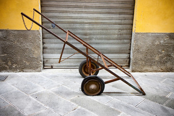 Old metal pushcart against a colored wall