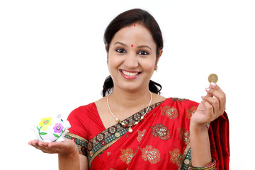 Traditional Indian woman holding a piggy bank and rupee coin