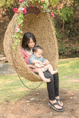 young asian mother holding baby on rattan swing