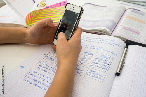 Leinwanddruck Bild sms en faisant ses devoirs