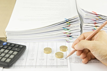 Man auditing account by pencil and gold coins with calculator