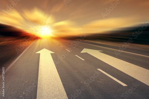 Leinwandbild Motiv arrow on the road with rising sun on background