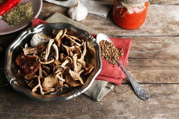 Dried mushrooms in metal tray with spices on wooden background