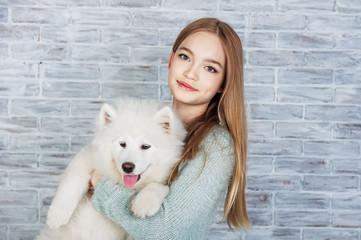 Beautiful girl huging Samoyed dog