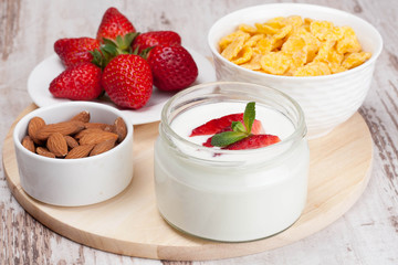 healthy breakfast - yogurt, fresh strawberries and cornflakes