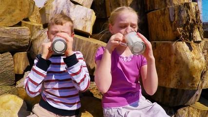 Boy and girl sitting on a tree stump drinking milk