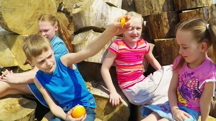 Four children 7-10 years laugh and eat oranges