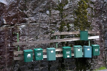 green mailboxes on stone wall