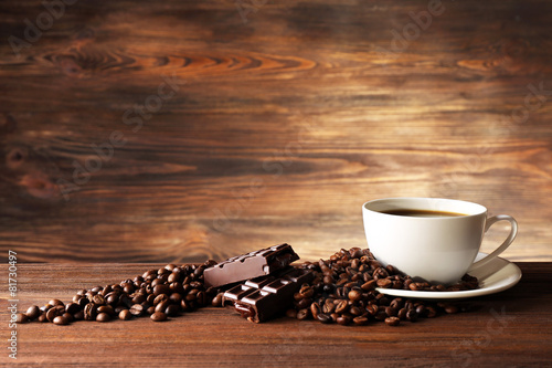 Cup of coffee with grains on wooden background - 81730497