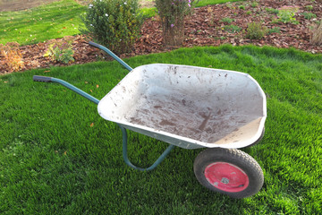 Modern two-wheeled wheelbarrow on the fresh lawn