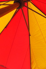 Giant red and yellow umbrella against a palm leaf