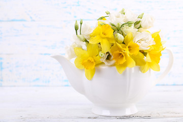 Beautiful bouquet of yellow daffodils and roses in teapot