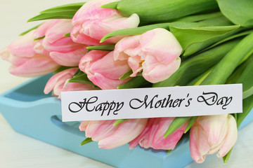 Happy Mother's day card with pink tulips on blue wooden tray