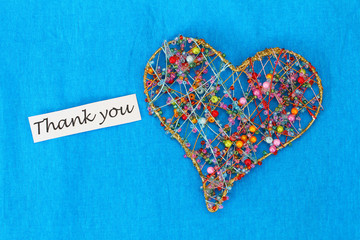 Thank you card with heart made of beads on blue background