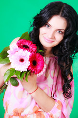 Beautiful young brunette in a pink dress with a bunch of flowers
