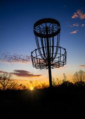 Disc golf basket against sunset