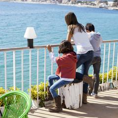 Niños apoyados en barandilla mirando el mar