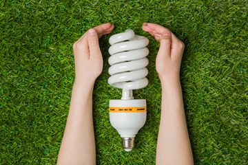Hands with energy saving eco lamp over grass