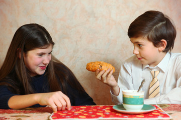 siblings sister and brother are naughty while eat croissant with