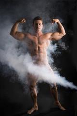 Totally naked male bodybuilder with smoke hiding genitalia