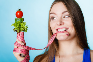 Woman biting measuring tape with vegetables.
