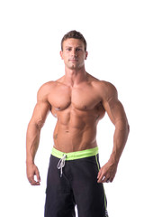 Muscular young bodybuilder in relaxed pose, smiling. Isolated