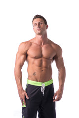 Muscular young bodybuilder in relaxed pose. Isolated