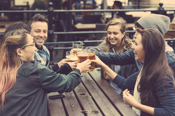 Group of friends enjoying a beer at pub in London