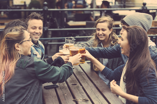 Group of friends enjoying a beer at pub in London - 81742610