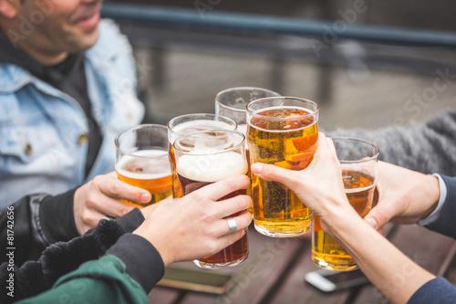 Leinwanddruck Bild Group of friends enjoying a beer at pub in London