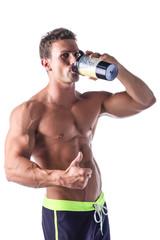 Muscular shirtless male bodybuilder holding protein shake bottle
