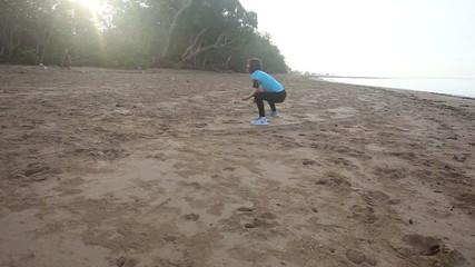girl starts doing morning exercises on beach at sunrise