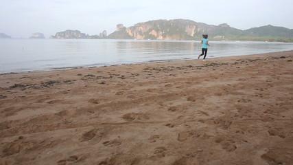 young european girl walks and starts to run along beach sunrice