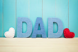 DAD text letters with hearts over blue wooden background