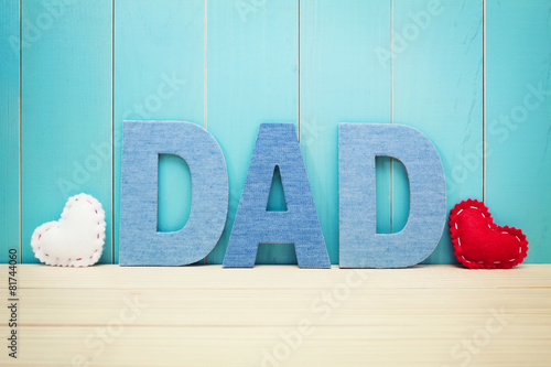 Leinwanddruck Bild DAD text letters with hearts over blue wooden background