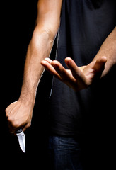 Close up of a robbers hands holding a knife in the shadows