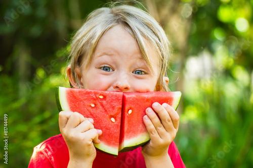Leinwanddruck Bild Funny happy child eating watermelon outdoors