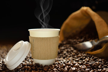 Paper cup of coffee with smoke and coffee beans on wooden table © amenic181